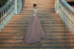 Senhora bonita no vestido luxuoso do salão de baile que anda acima das escadas de seu palácio fotos de stock royalty free