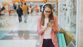 A senhora bonita nos fones de ouvido está escutando a música e está usando o smartphone que anda no shopping com sacos de papel m vídeos de arquivo