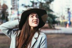 A senhora bonita nova em um chapéu olha felizmente acima & sorri imagem de stock royalty free