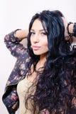 A senhora bonita nova moreno 'sexy' com cabelo longo na flor imprimiu o casaco de cabedal que tem o divertimento que olha sensual imagens de stock royalty free