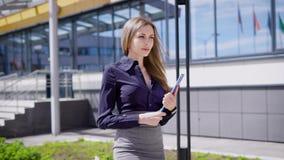 A senhora bonita nova na blusa azul e na saia cinzenta com a prancheta nas mãos está andando fora perto do prédio de escritórios filme