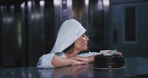 A senhora bonita nova vestida em um vestuário completo dos cozinheiros chefe colocou a cereja de travamento do olho vermelho em s video estoque