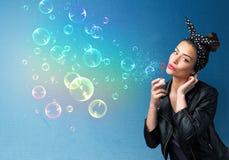 Senhora bonita que funde bolhas coloridas no fundo azul Imagens de Stock