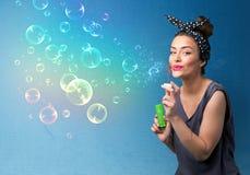 Senhora bonita que funde bolhas coloridas no fundo azul Imagem de Stock