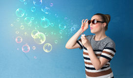Senhora bonita que funde bolhas coloridas no fundo azul Foto de Stock Royalty Free