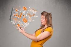 Senhora bonita que guarda o caderno com gráficos e estatísticas Foto de Stock