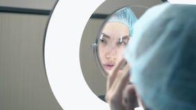 A senhora bonita verifica a tatuagem da testa com a régua no espelho leve filme