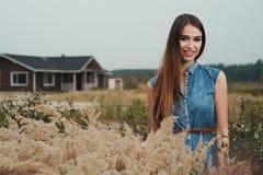 Senhora bonito do campo que está na grama alta contra a casa de rancho Fotografia de Stock Royalty Free