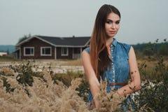 Senhora bonito do campo que está na grama alta contra a casa de rancho Imagens de Stock Royalty Free
