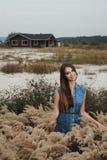 Senhora bonito do campo que está na grama alta contra a casa de rancho Imagens de Stock