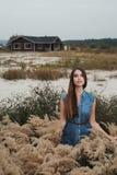Senhora bonito do campo que está na grama alta contra a casa de rancho Fotos de Stock