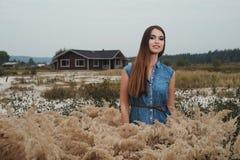 Senhora bonito do campo que está na grama alta contra a casa de rancho Foto de Stock