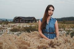 Senhora bonito do campo que está na grama alta contra a casa de rancho Imagem de Stock Royalty Free