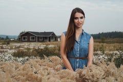 Senhora bonito do campo que está na grama alta contra a casa de rancho Fotos de Stock Royalty Free