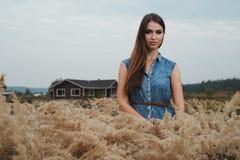 Senhora bonito do campo que está na grama alta contra a casa de rancho Foto de Stock Royalty Free