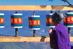 Senhora butanesa idosa e rodas de oração tibetanas de madeira velhas na passagem do la de Chele, Butão imagens de stock