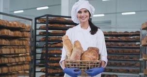 Senhora carismática da indústria de padaria com uma cesta grande do pão orgânico no meio da máquina industrial que olha em linha  vídeos de arquivo