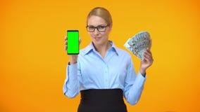Senhora caucasiano bonita que mostra o smartphone da tela e dólares verdes, dinheiro para trás filme