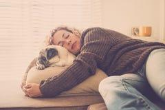 A senhora caucasiano dorme em casa abra?ando seu pug claro velho do melhor amigo bonito no sof? - conceito do amor e da amizade p fotografia de stock royalty free