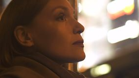 Senhora caucasiano pensativa que espera na parada do ônibus, olhando o close-up iluminado da cidade video estoque