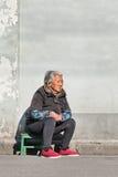 A senhora chinesa idosa senta-se fora em uma cadeira de madeira pequena Foto de Stock
