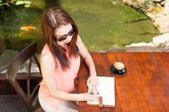 Senhora com máscaras na escrita na agenda no terraço Imagem de Stock