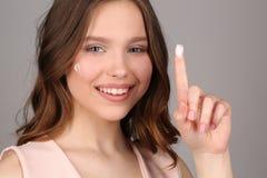 Senhora com o creme que mostra um dedo Fim acima Fundo cinzento Fotos de Stock Royalty Free