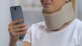Senhora com o smartphone na dor de pescoço cervical do sentimento do colar da espuma, reabilitação filme