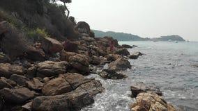 Senhora com suportes do cabelo escuro na pedra enorme contra o mar azul filme