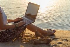 Senhora com um portátil na praia Fotografia de Stock Royalty Free