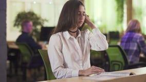 Senhora concentrada que senta-se no escritório moderno decorado em tons verdes e que lê o compartimento Dia usual do escritório f vídeos de arquivo