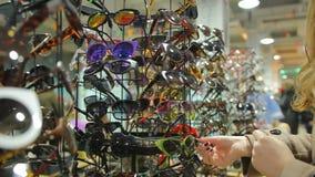 A senhora confundida com a grande escolha dos óculos de sol na compra está no mercado local video estoque