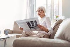 Senhora consideravelmente superior que está sendo imergida no jornal da leitura imagens de stock royalty free