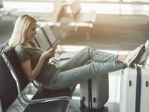 Senhora contente que nota no móbil antes da viagem Imagem de Stock