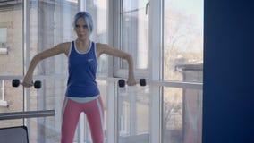 Senhora da aptidão que faz o exercício lateral do aumento do peso no gym vídeos de arquivo