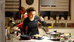 A senhora da mulher prepara o alimento na cozinha na empresa de seus amigos vídeos de arquivo