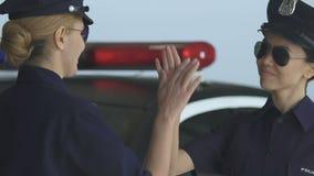 Senhora da polícia que faz a gesto alto-cinco relações confiantes na igualdade de gênero do pelotão video estoque