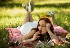Senhora de cabelo vermelha que encontra-se no véu na grama que come a morango e que lê um livro Fotografia de Stock Royalty Free