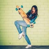 Senhora de cabelos compridos bonita com um longboard de madeira perto de um verde Foto de Stock
