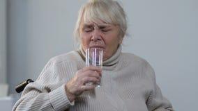 Senhora de envelhecimento na cadeira de rodas que toma o comprimido e a água potável, hipertensão filme