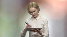 Senhora de meia idade do negócio que tira na tabuleta digital filme