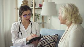 Senhora de pessoa idosa de visita da enfermeira em suas casa e tabuleta da utilização video estoque