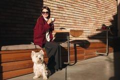 Senhora de sorriso bonita nos óculos de sol que bebe o café que senta-se no café da rua com seu cão bonito pequeno foto de stock royalty free