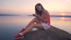 A senhora de sorriso está sentando-se em uma rocha em um banco com seu smartphone vídeos de arquivo