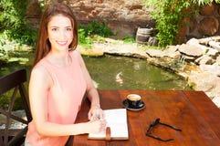 Senhora de sorriso na escrita do terraço no caderno Fotografia de Stock Royalty Free