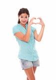 A senhora de sorriso nas calças de brim curtos que fazem um amor assina Fotos de Stock