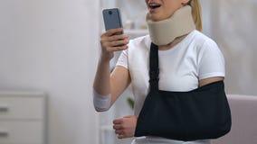 Senhora de sorriso no estilingue cervical do colar e do braço que datilografa no smartphone, recuperação video estoque