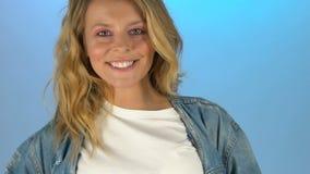 Senhora de sorriso no fundo azul, modelo que levanta para o tiro da forma, lento-movimento filme