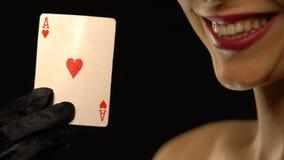 Senhora de sorriso que mostra o ás de corações na câmera, isolado no fundo preto video estoque