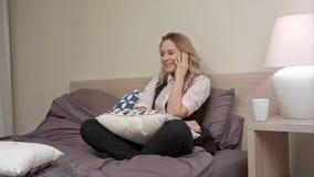A senhora de sorriso tem a conversação no smartphone em casa em horas de dormir Fotos de Stock Royalty Free